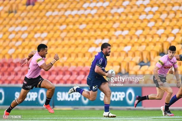 In this handout image provided by NRL Photos Kenneath Bromwich of the Storm runs with the ball as empty seats are seen in the background during the...