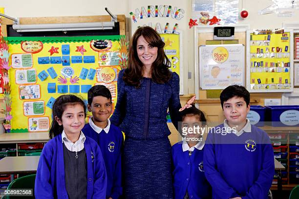 In this handout image provided by Place2Be, Catherine, Duchess of Cambridge poses for a photo with Nimra Ryan Bailey-Rae and Connor from Salusbury...