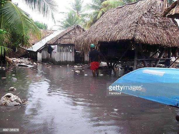 In this handout image provided by Plan International Australia a man stands in flood waters March 13 2015 on the island of Kiribati Cyclone Pam is...
