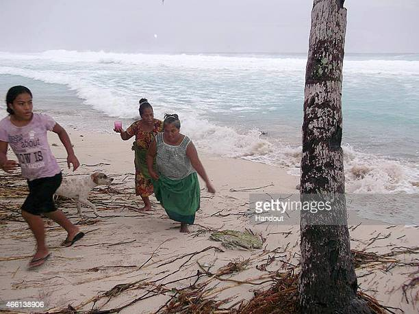 In this handout image provided by Plan International Australia people move away from the beach March 13 2015 on the island of Kiribati Cyclone Pam is...