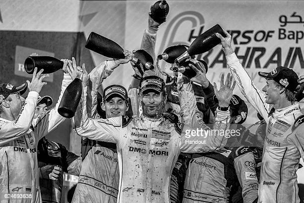 In this handout image provided by Red Bull #1 Porsche LMP1 car driver Mark Webber of Australia is doused in rose water by his team mates and...