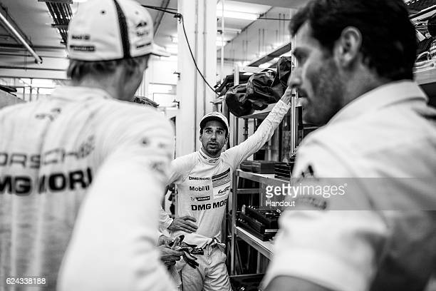 In this handout image provided by Red Bull, #2 Porsche LMP1 car driver Neel Jani of Switzerland talks with car drivers Mark Webber of Australia and...