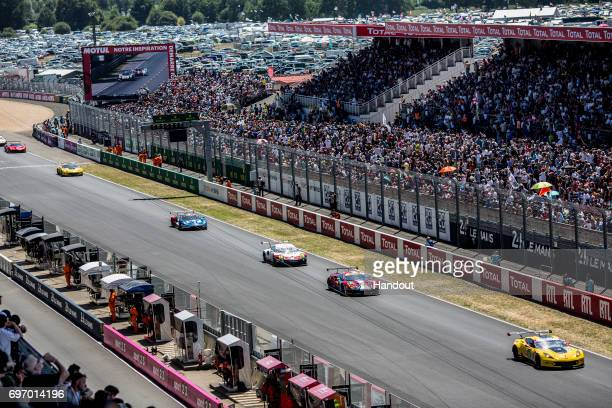 In this handout image provided by Red Bull A Corvette C7R Ferrari 488 Porsche 911 RSR and Ford GT run down the start/finish straight to start their...