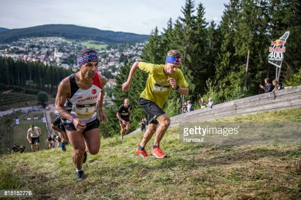 In this handout image provided by Red Bull Ahmet Arslan of Turkey and Anton Palzer of Germany make their way up the 400 metre long ski jump course...