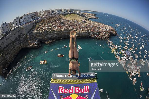 In this handout image provided by Red Bull Alessandro de Rose of Italy prepares to launch an armstand dive from the 27 metre platform during the...