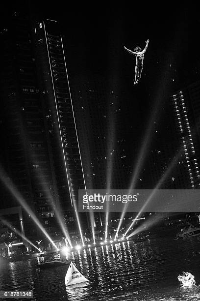 In this handout image provided by Red Bull Andrei Mikau of Belarus dives from the 27 metre platform on the Dubai Marina Pier 7 building during the...