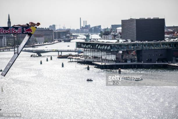 In this handout image provided by Red Bull Andy Jones of the USA looks down from the 27 metre platform on the roof of the Opera House during the...