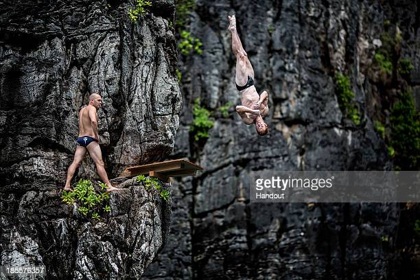 In this handout image provided by Red Bull Andy Jones of the USA dives from the 10 metre platform at Maya Bay as Kent De Mond of the USA watches on...