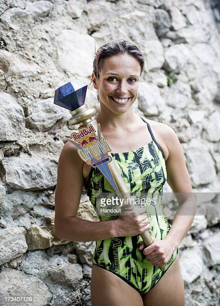 In this handout image provided by Red Bull Anna Bader of Germany poses with the winners trophy at the Scaliger Castle during the first Red Bull Cliff...