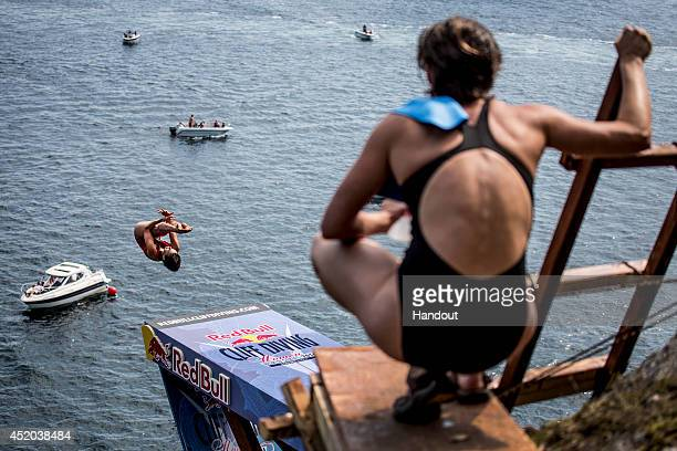 In this handout image provided by Red Bull Anna Bader of Germany dives from the 20 metre platform as Ginger Huber of the United States watches on...