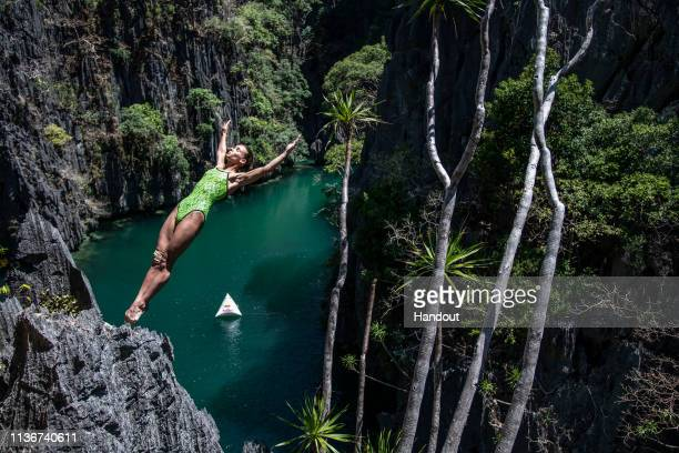 In this handout image provided by Red Bull Antonina Vyshyvanova of Ukraine dives from a rock precipice at the Small Lagoon on Miniloc Island during...