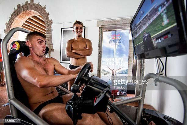 In this handout image provided by Red Bull Artem Silchenko of Russia tries out the F1 game in the athletes lounge at Scaliger Castle while Anatoliy...
