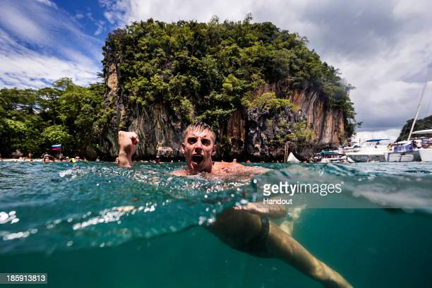 In this handout image provided by Red Bull Artem Silchenko of Russia celebrates after his final dive from the 27 metre platform on Hong Island in the...