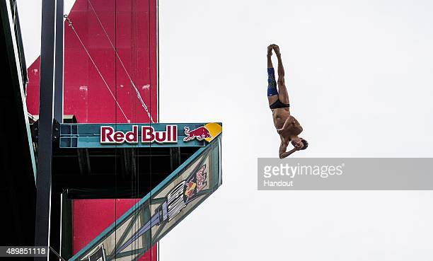 In this handout image provided by Red Bull Blake Aldridge of the UK dives from the 275 metre platform on La Salve bridge during the first training...