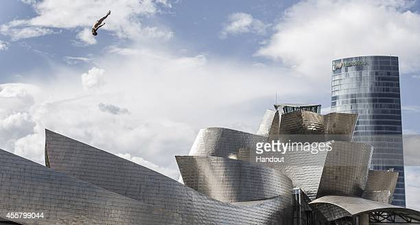 In this handout image provided by Red Bull Cyrille Oumedjkane of France dives from the 27 metre platform on La Salves Bridge next to the Guggenheim...