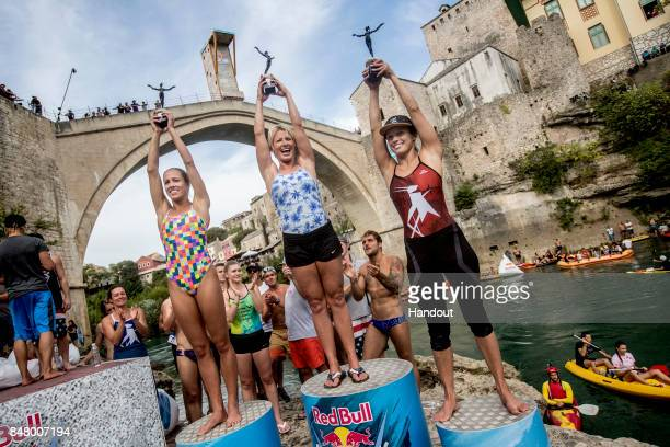 In this handout image provided by Red Bull Herlena Merten of Australia Cesilie Carlton of the USA and Anna Bader of Germany celebrate on the podium...