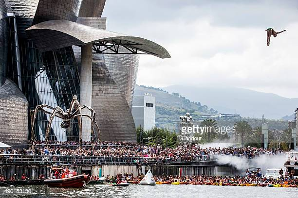 In this handout image provided by Red Bull Jucelino Junior of Brazil dives from the 275 metre platform on La Salve bridge during the eighth and final...