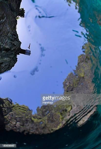 In this handout image provided by Red Bull Michal Navratil of the Czech Republic dives from the 27 metre platform at Maya Bay in the Andaman Sea...
