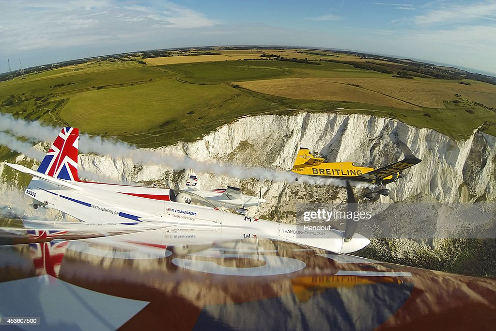 In this handout image provided by Red Bull, Nigel Lamb and Paul Bonhomme of Great Britain fly in formation with Matthias Dolderer of Germany prior to the fifth stage of the Red Bull Air Race World Championship in front of the cliffs of Dover on August 14, 2014 near Dover, United Kingdom.