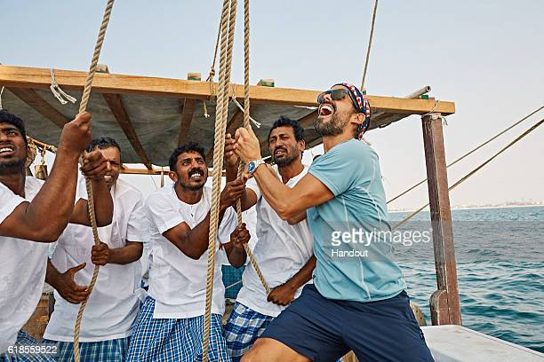 In this handout image provided by Red Bull Orlando Duque of Colombia assists the crew to raise the sail while sailing on a traditional fishing dhow...