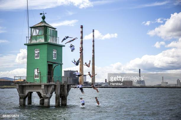 In this handout image provided by Red Bull Orlando Duque of Colombia and Anna Bader of Germany dive off the iconic Northbank Lighthouse in buildup to...