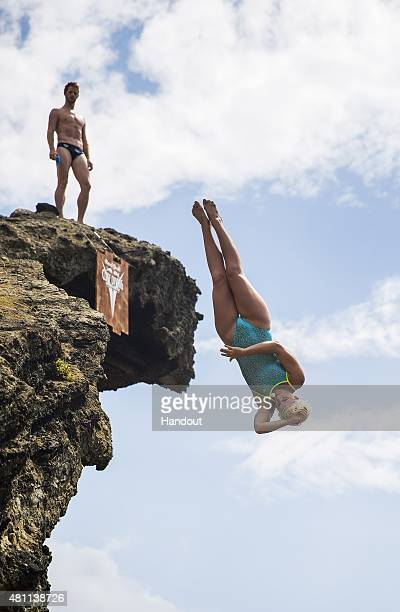 In this handout image provided by Red Bull Rachelle Simpson of the USA dives from the Snakehead rock while Andy Jones of the USA watches on during an...