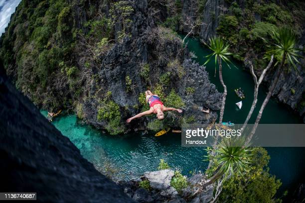 In this handout image provided by Red Bull Rhiannan Iffland of Australia dives from a rock pinnacle at the Small Lagoon on Miniloc Island during the...