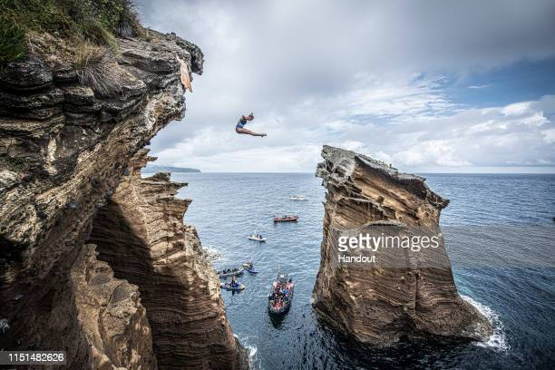 In this handout image provided by Red Bull, Rhiannan Iffland of Australia dives from a 21 metre cliff at the Snakehead on Islet Vila Franco do Campo...