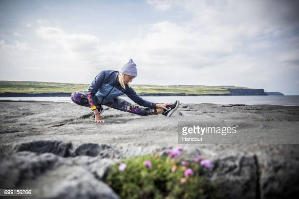 In this handout image provided by Red Bull Rhiannan Iffland of Australia prepares to dive 20 metres from a helicopter at the Cliffs of Moher in...