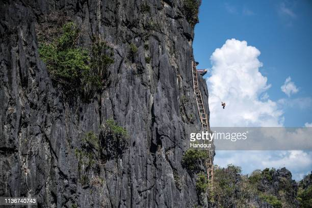 In this handout image provided by Red Bull Sergio Guzman of Mexico dives from the 27 metre platform at the Big Lagoon on Miniloc Island during the...