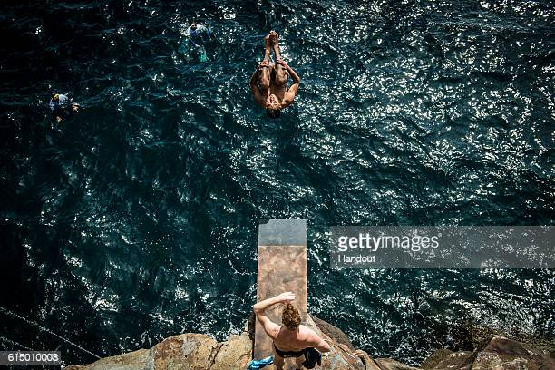 In this handout image provided by Red Bull Sergio Guzman of Mexico dives from the 6 metre practice platform while Alain Kohl of Luxembough watches on...