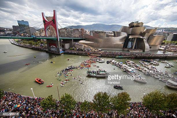 In this handout image provided by Red Bull Spectators watch as Jonathan Paredes of Mexico dives from the 27 metre platform on La Salves Bridge next...