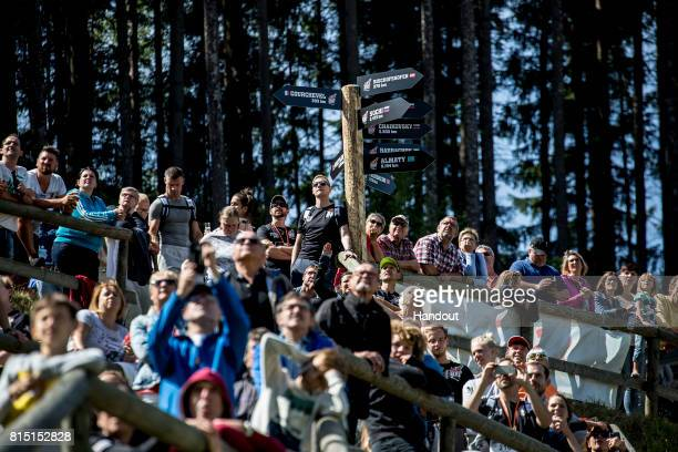 In this handout image provided by Red Bull Spectators watch the competitors make their way up the 400 metre long ski jump course with 140 metres of...