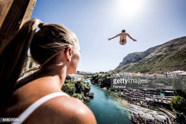 In this handout image provided by Red Bull Steven LoBue of the USA dives from the 27 metre platform on Stari Most while Helena Merten of Australia...