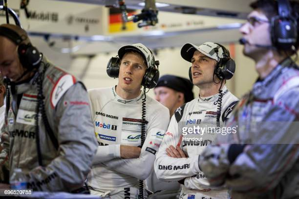 In this handout image provided by Red Bull The Porsche LMP1 919 Hybrid drivers Brendon Hartley and Earl Bamber of New Zealand watch the timing...