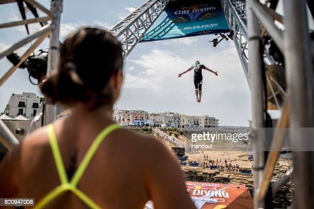 In this handout image provided by Red Bull Viktar Maslouski of Belarus dives from the 27 metre platform as Anna Bader of Germany watches on from the...