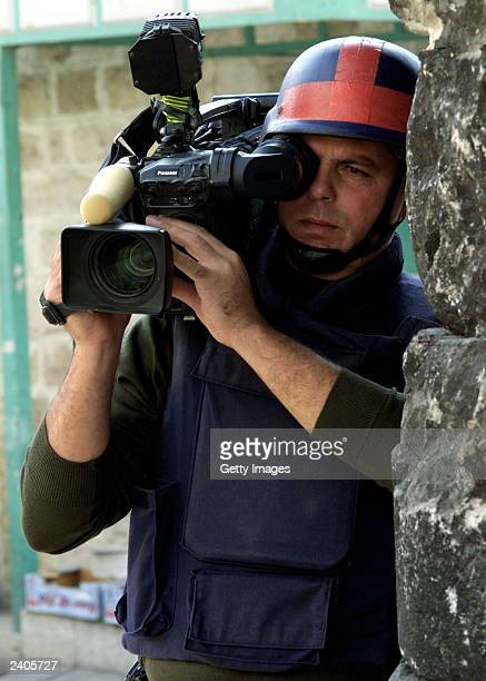 In this handout image provided by Reuters cameraman Mazen Dana is shown working October 18 2001 in the West Bank city of Hebron Witnesses state that...