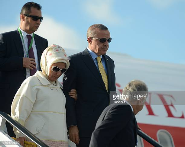 In this handout image provided by Ria Novosti Prime Minister of the Republic of Turkey Recep Tayyip Erdogan and his wife Emine Erdogan arrive in...