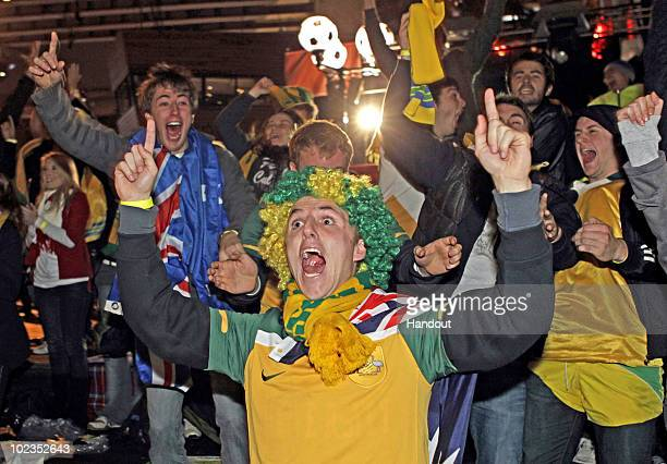 In this handout image provided by Rick Stevens/FIFA Fan Fest Australian fan Andrew Sylvester of TareeNSW reacts to Australia's first goal during the...