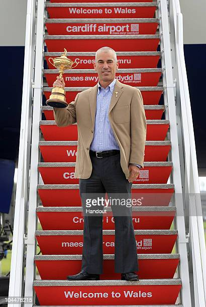 In this handout image provided by Ryder Cup Europe USA team captain Corey Pavin holding the Ryder Cup trophy arrives with the USA team at Cardiff...