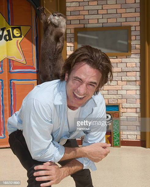 In this handout image provided by SeaWorld San Diego actor Dermot Mulroney is all smiles as he gives OP Otter a boost during his visit to SeaWorld...