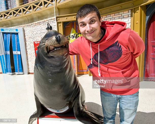 In this handout image provided by SeaWorld San Diego SeaWorld San Diego's star sea lion Clyde shares a smile with 'My Chemical Romance' guitarist...