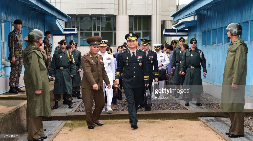 In this handout image provided by South Korean Defense Ministry, South Korean Major Gen. Kim Do-gyun (R) is escorted by a North Korean officer after crossing the military demarcation line (MDL) for the meeting on June 14, 2018 in Panmunjom, North Korea. Two Koreas began their first high-level military talks in more than 10 years to discuss ways to ease cross-border tensions.