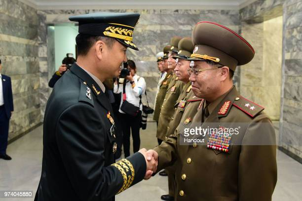 In this handout image provided by South Korean Defense Ministry South Korean Major Gen Kim Dogyun shakes hands with his North Korean counterpart Lt...