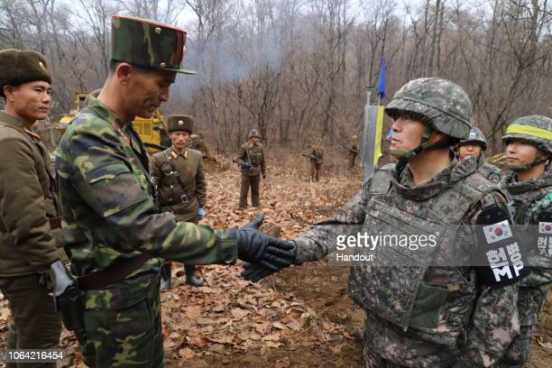 In this handout image provided by South Korean Defense Ministry today taken on an unconfirmed date a South Korean soldier shakes hands with a North...