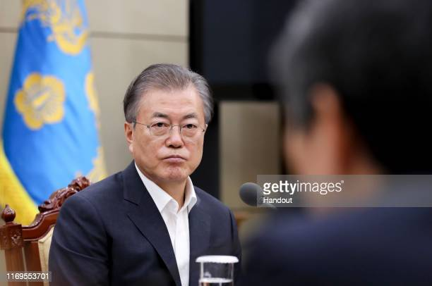 In this handout image provided by South Korean Presidential Blue House, South Korean President Moon Jae-in listens to a report from officials related...