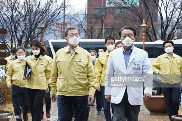 In this handout image provided by South Korean Presidential Blue House South Korean President Moon Jaein talks to a president of Daegu Medical Center...