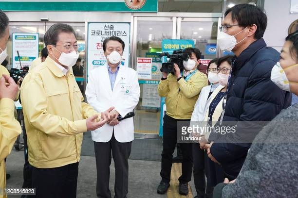 In this handout image provided by South Korean Presidential Blue House, South Korean President Moon Jae-in, meets with medical members at the Daegu...