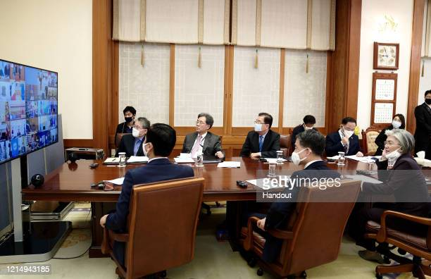 In this handout image provided by South Korean Presidential Blue House, Presidential staffs watch a screen showing G-20 virtual summit to discuss the...