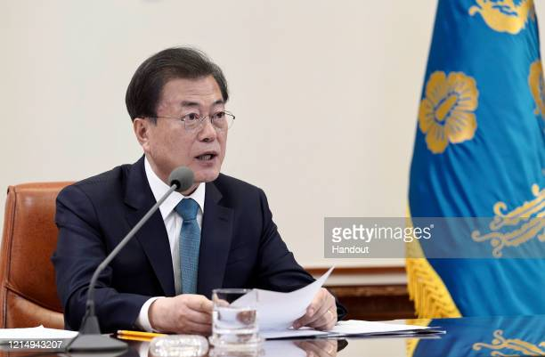 In this handout image provided by South Korean Presidential Blue House, South Korean President Moon Jae-in discuss with global leaders on a...